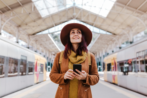 Young tourist woman at train station waiting to take a train and travel. using mobile phone and smiling Premium Photo