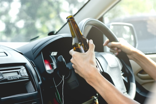 Young tourists are driving while drinking alcohol. Premium Photo