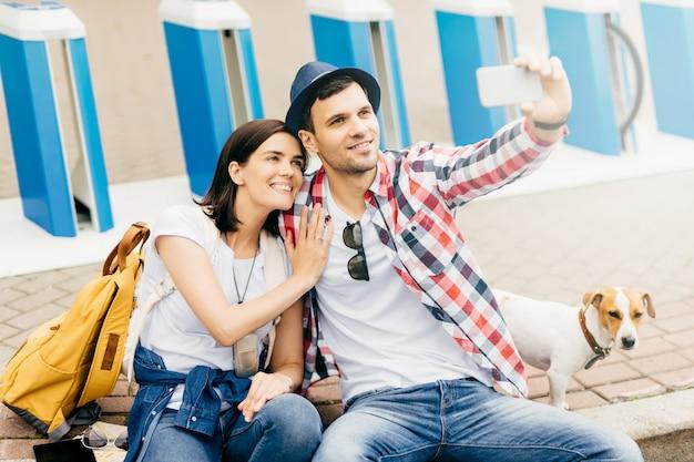 舗装の上に座って、スマートフォンでselfieを作り、幸せな表情でカメラにポーズをとって、美術館や美術館を訪れた後に休む若い観光客。男性と女性の休憩、撮影 Premium写真