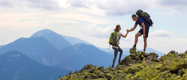 Young tourists with backpacks, athletic boy helps slim girl to clime rocky mountain top against bright summer sky and mountain range background. tourism, traveling and healthy lifestyle concept. Premium Photo