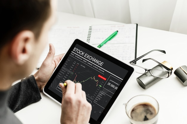 Young trader is sitting in home at table, working on tablet with graphs Premium Photo