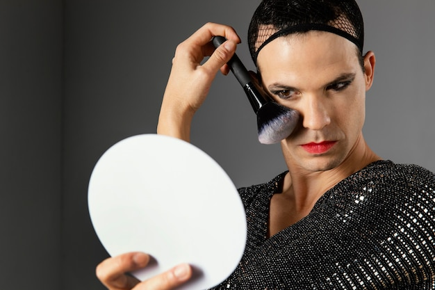 메이크업 브러시를 사용하는 젊은 트랜스젠더 사람 무료 사진
