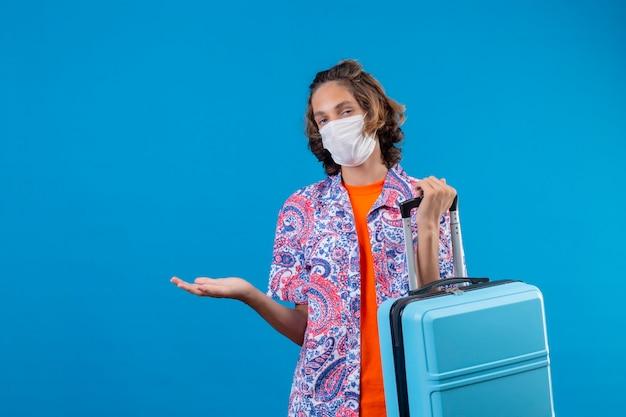 Ragazzo giovane viaggiatore che indossa la maschera protettiva per il viso tenendo la valigia di viaggio all'oscuro e confuso in piedi con il braccio alzato su sfondo blu Foto Gratuite