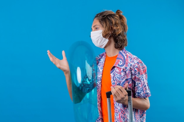 Ragazzo giovane viaggiatore che indossa la maschera protettiva facciale che tiene la valigia di viaggio e l'anello gonfiabile che osserva da parte con l'espressione sicura seria che sta con il braccio alzato sopra fondo blu Foto Gratuite