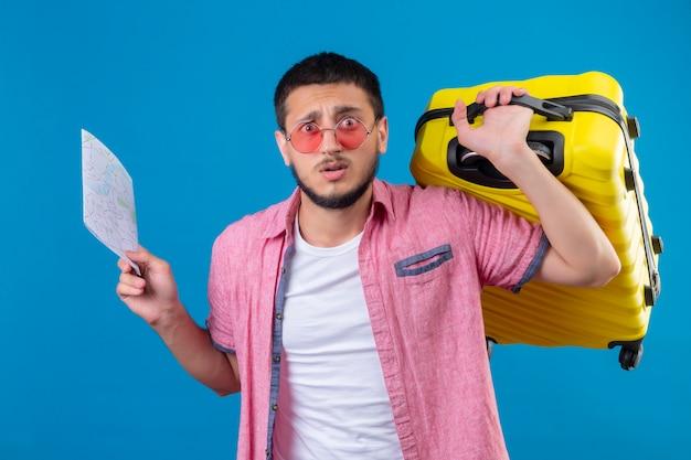 Молодой путешественник красивый парень в солнечных очках держит карту и дорожный чемодан, выглядит смущенным и разочарованным, стоя на синем фоне Бесплатные Фотографии