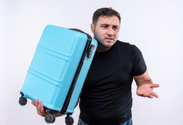Uomo del giovane viaggiatore in maglietta nera che tiene la valigia che osserva da parte in piedi confuso e molto ansioso sopra il muro bianco Foto Gratuite