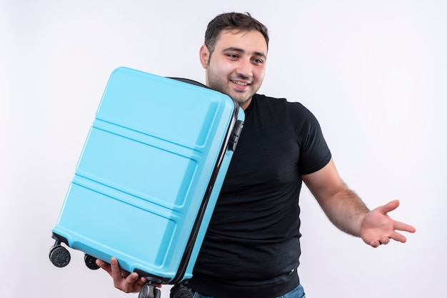 Young traveler man in black t-shirt holding suitcase looking aside smiling cheerfully spreading with arm to the side standing over white wall Free Photo