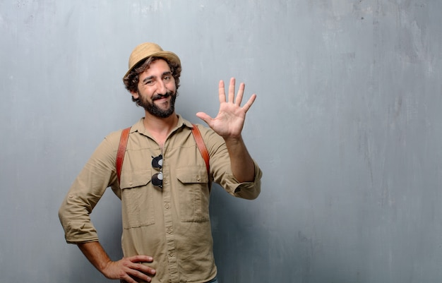 Young traveler man or tourist smiling, counting number five with fingers, with an open palm Premium Photo