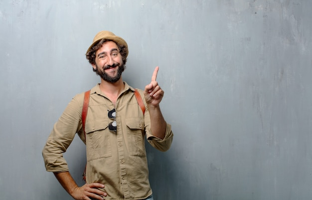 Young traveler man or tourist smiling and looking satisfied and happy, number one Premium Photo