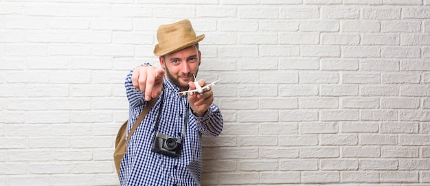 Young traveler man wearing backpack and a vintage camera cheerful and smiling pointing to the front. Premium Photo
