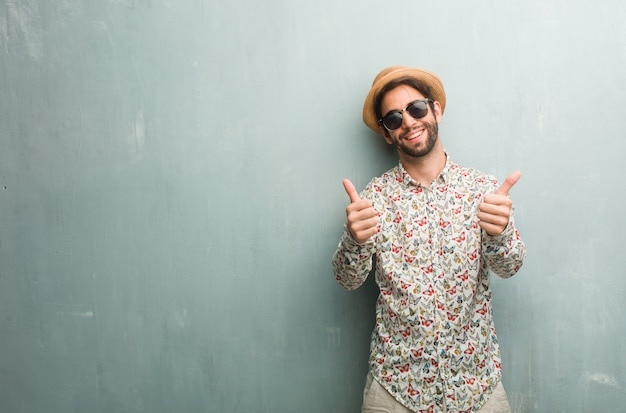 Young traveler man wearing a colorful shirt cheerful and excited, smiling and raising her thumb up, concept of success and approval, ok gesture Premium Photo
