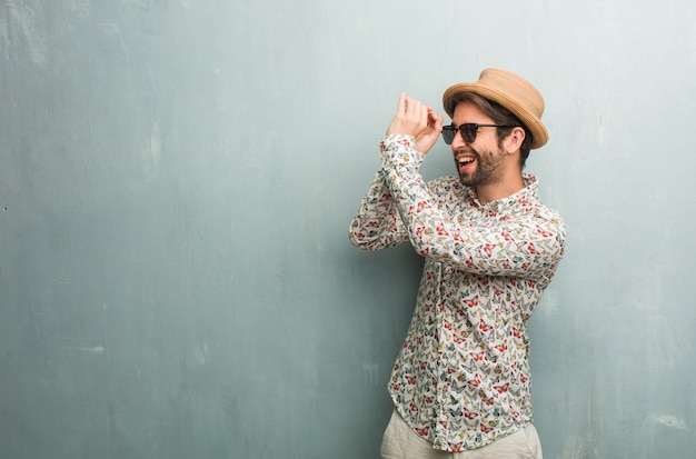 Young traveler man wearing a colorful shirt looking through a gap, hiding and squinting Premium Photo