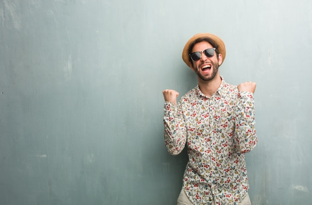 Young traveler man wearing a colorful shirt very happy and excited, raising arms Premium Photo