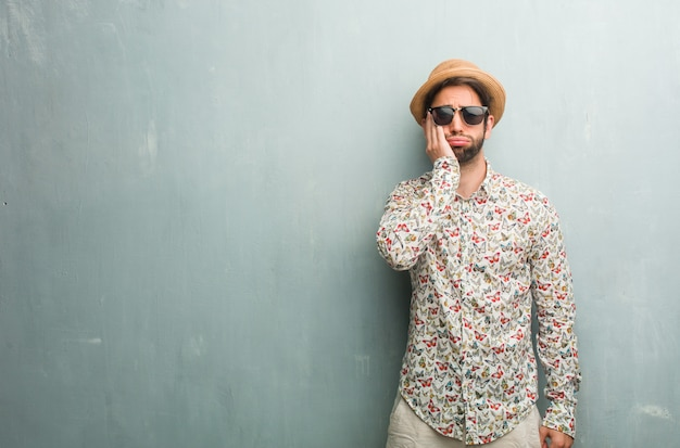 Young traveler man wearing a colorful shirt worried and overwhelmed, forgetful Premium Photo