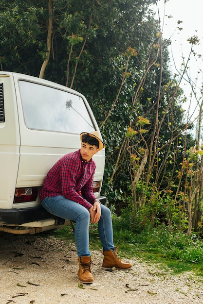 Young traveler siting on back of van Free Photo