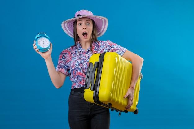 青い背景上の恐怖の間違い式のための恥でショックを受けたカメラを見て目覚まし時計を保持している黄色のスーツケースを持って夏帽子立っている若い旅行者女性 無料写真