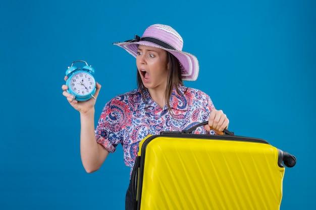 それを見て目覚まし時計を保持している黄色のスーツケースと夏の帽子立っている若い旅行者女性 無料写真