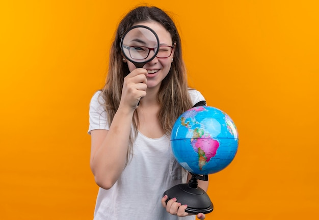 オレンジ色の壁の上に驚いて幸せに立っている拡大鏡を通して見ている地球を保持している白いtシャツの若い旅行者の女性 無料写真