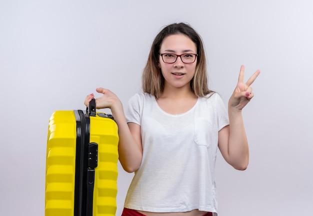 白い壁の上に立っている勝利のサインを示す幸せでポジティブなスーツケースを保持している白いtシャツの若い旅行者の女性 無料写真