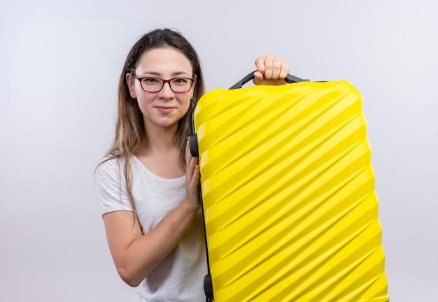 白い壁の上に立って幸せで前向きな笑顔のスーツケースを保持している白いtシャツの若い旅行者の女性 無料写真