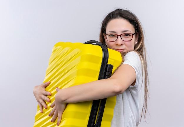 白い壁の上に前向きで幸せな笑顔で彼女のスーツケースを抱き締めるスーツケースを保持している白いtシャツの若い旅行者の女性 無料写真