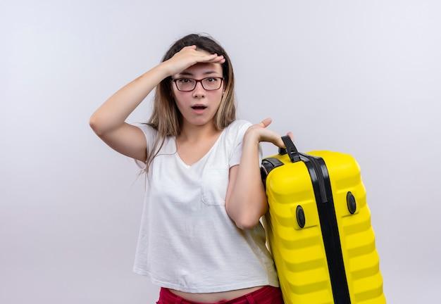 白い壁の上に立って驚いて驚いたように見えるスーツケースを保持している白いtシャツの若い旅行者の女性 無料写真