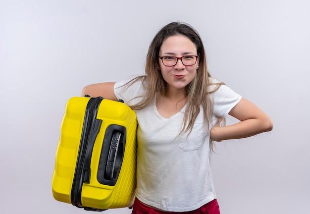 白い壁の上に立って楽しく幸せな笑顔に見えるスーツケースを保持している白いtシャツの若い旅行者の女性 無料写真