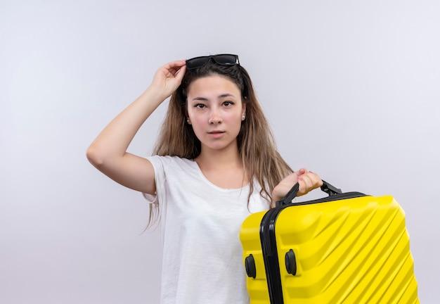 白い壁の上に立って困惑しているように見えるスーツケースを保持している白いtシャツの若い旅行者の女性 無料写真