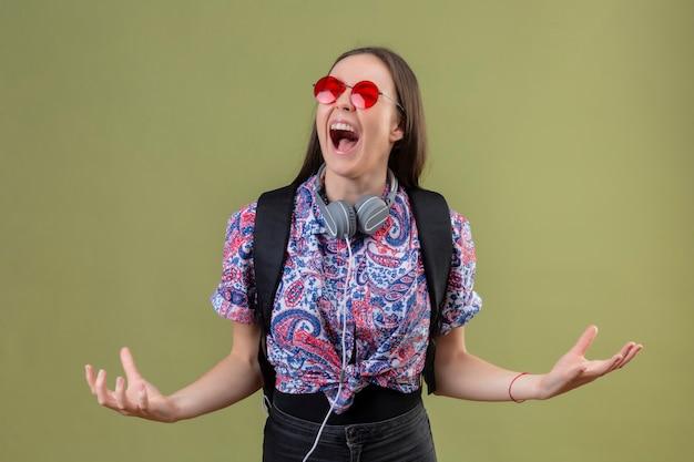 Молодая женщина-путешественница, стоящая с рюкзаком и наушниками в красных солнцезащитных очках, сумасшедшая и безумная, кричит с агрессивным выражением лица и поднятыми руками на зеленом фоне Бесплатные Фотографии