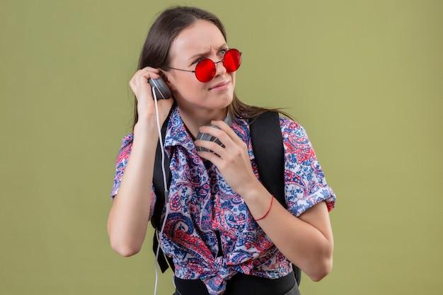 赤いサングラスをかけている若い旅行者の女性と緑の壁に顔をしかめ顔をして不快なヘッドフォンを使用して音楽を聴くバックパック 無料写真