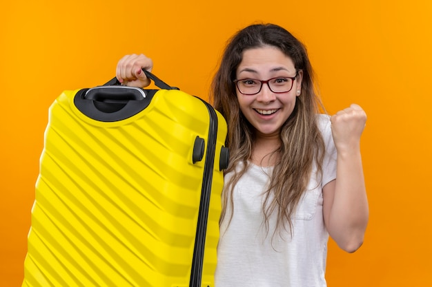 Young traveler woman in white t-shirt  holding suitcase excited and happy clenching fist standing over orange wall Free Photo