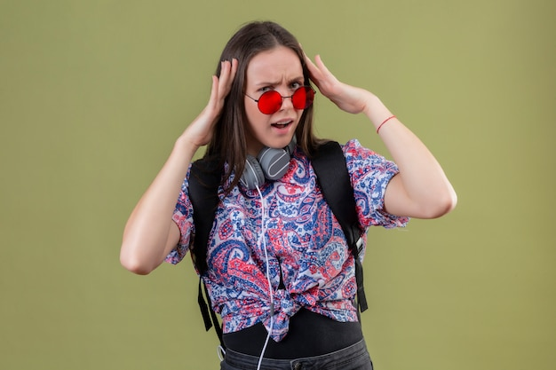 Young traveler woman with backpack and headphones wearing red sunglasses touching head looking annoyed having headache standing over green wall Free Photo