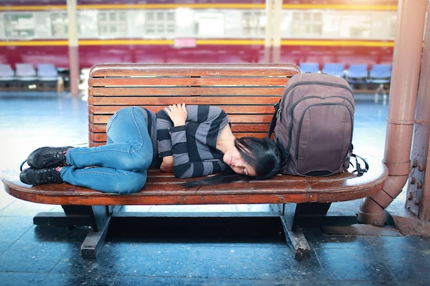 Young traveler woman with backpack sleeping and waiting for train Premium Photo