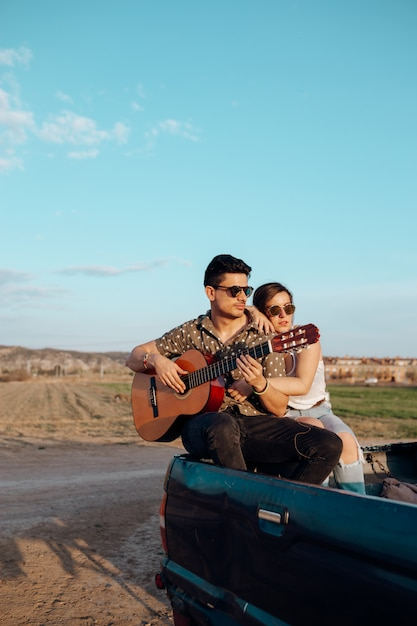 Young travelers lovers having fun playing the guitar on top of jeep 4x4 car. couple making a wanderlust vacation at summer Premium Photo
