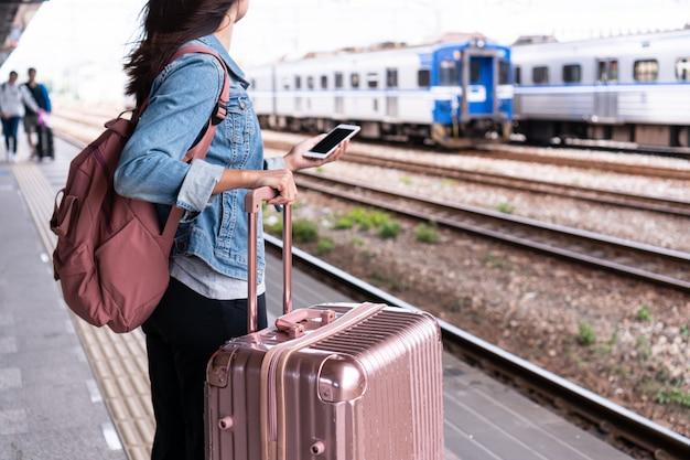 Молодая девушка путешественника в джинсовой куртке с концепцией смарт-телефона, розовой сумки и багажа ждать поезда на концепции платформы, космоса экземпляра, перемещения или транспорта Premium Фотографии