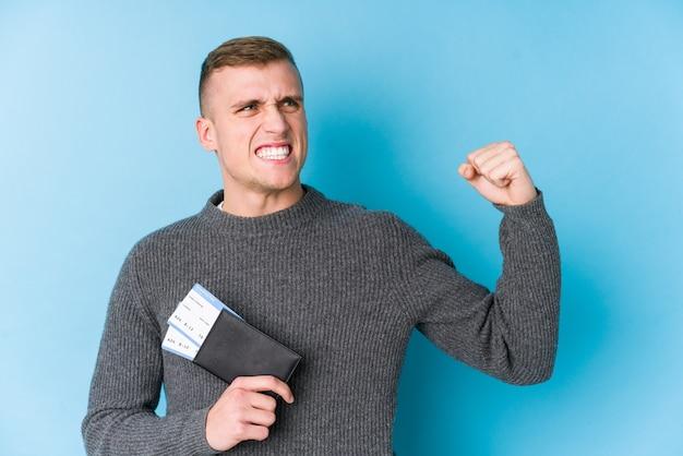 Молодой путешественник, держащий посадочный талон, поднимает кулак после победы Premium Фотографии
