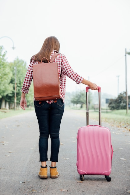 Young traveller with backpack and pink luggage Free Photo