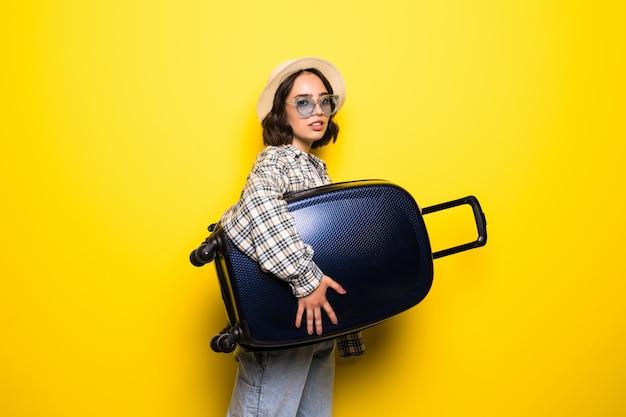 Молодая тенденция женщина в солнечных очках и соломенной шляпе готова к летнему путешествию изолирована Бесплатные Фотографии