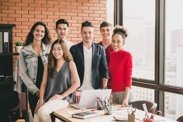 Young trendy diverse smiling millennial team in casual clothes around office table Premium Photo