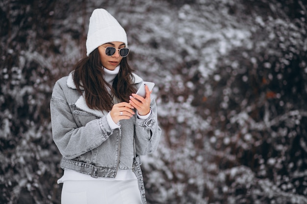 Young trendy girl in a winter park using phone Free Photo