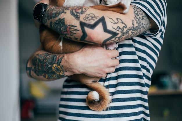 문신 미친 곱슬 머리를 가진 젊은 유행 힙 스터는 그의 작은 가장 친한 친구를 껴안고 무료 사진