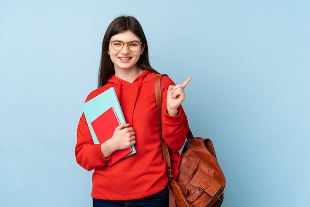 Young ukrainian teenager student girl holding a salad over isolated blue wall pointing finger to the side Premium Photo