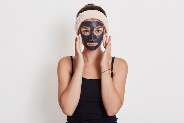 Giovane casalinga infelice con maschera cosmetica nera sul viso in piedi isolato su un muro bianco, toccando le guance con le dita Foto Gratuite