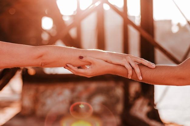 日没の屋外で手を繋いでいる認識できないレズビアンカップル Premium写真