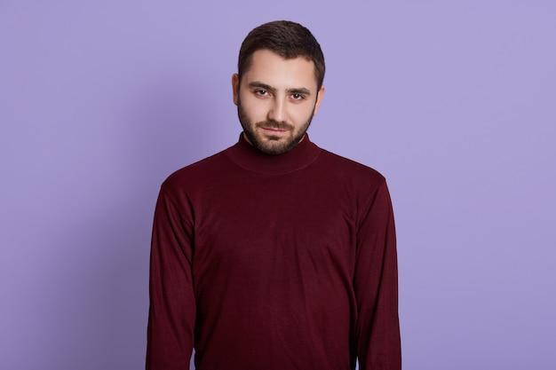 Молодой небритый мужчина в бордовом свитере позирует на фиолетовом фоне с серьезным выражением лица Бесплатные Фотографии