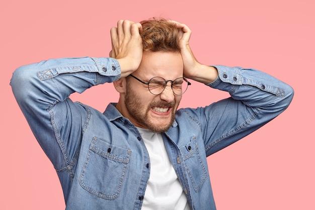 Молодой небритый стрессовый мужчина страдает головной болью, держит руки на висках, стискивает зубы, испытывает ужасную боль, закрывает глаза Бесплатные Фотографии