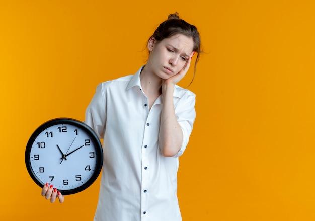 La giovane ragazza russa bionda sconvolta mette la mano sulla faccia che tiene l'orologio isolato sullo spazio arancione con lo spazio della copia Foto Gratuite