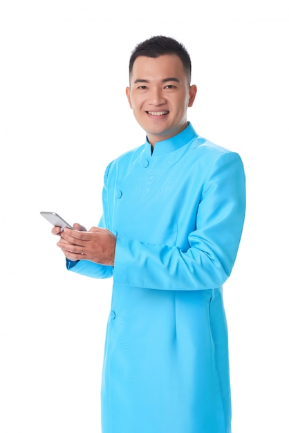 Young vietnamese man in traditional attire posing in studio and using smartphone Free Photo