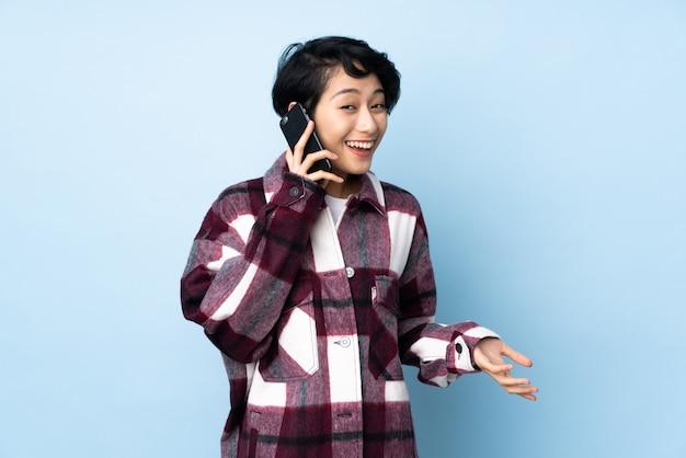 Молодая вьетнамская женщина с короткими волосами над стеной ведет разговор с кем-то по мобильному телефону Premium Фотографии