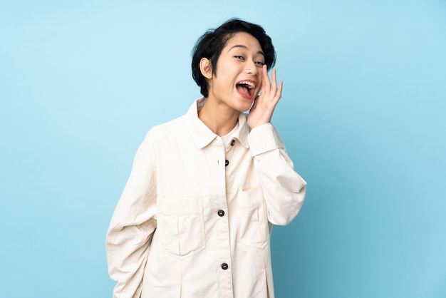 Young vietnamese woman with short hair over wall shouting with mouth wide open Premium Photo